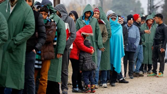 Menschen in Mänteln mit Mützen und Schals stehen in einer Reihe.