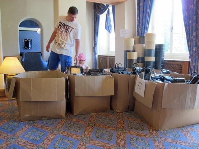 Mann betrachtet mit Kind elektronische Geräte in Schachteln
