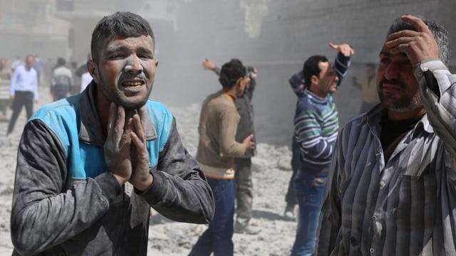 Menschen vor zerstörten Gebäuden, sie sehen verzweifelt aus.