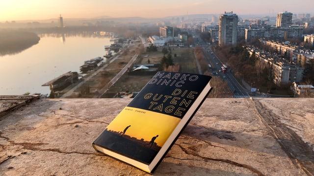 Der Roman «Die guten Tage» von Marko Dinić liegt auf einem Fenstersims von dem man über Belgrad blickt.