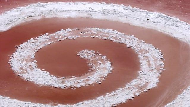 Durch das Wasser eines brau-rot schimmernden Sees zieht eine Salzspur einen mehrfach gewickelten Kringel.