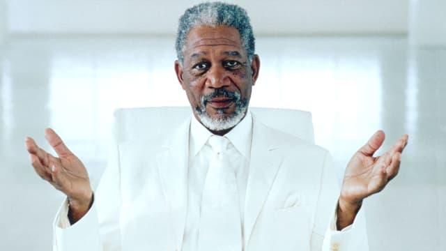 Morgan Freeman in weissem Anzug und mit geöffneten Händen.