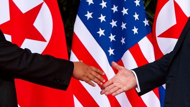 Duas persunas che dattan il maun avant bandiera dals Stadis Unids e da la China.