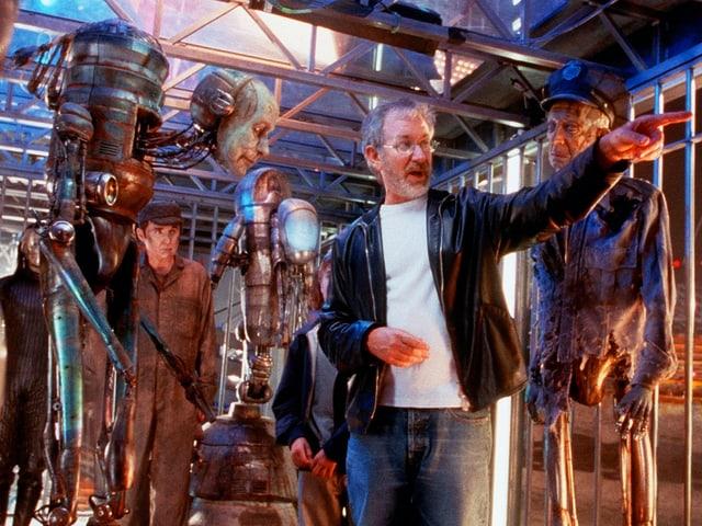 Steven Spielberg gestikuliert auf dem Set umgeben von Robotern in einem Käfig.