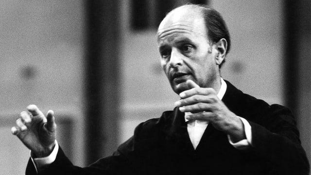 Der Dirigent Ferenc Fricsay dirigiert: seine Hände sind vor seinem Körper gehoben.