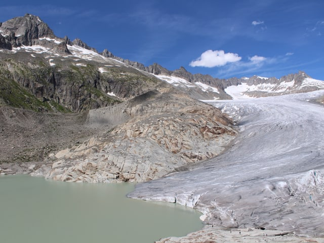 Rhonegletscher mit dem See, hinten eine Bergkette und blauer Himmel.