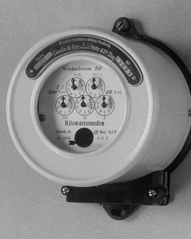 Ein weisser, runder Stromzähler mit fünf Zifferblättern und kleinen Zeigern.