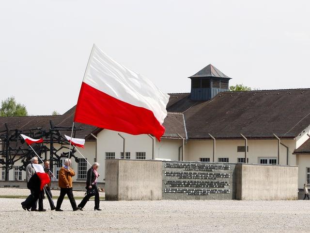Polnische Bürger laufen durch das ehemalige KZ mit Landesflaggen in den Händen.