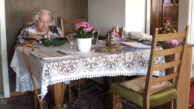 Eine alte Frau sitzt am Tisch mit Häckeldecke darauf, der Stock hängt am Tisch.