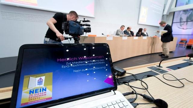PC an einer Medienkonferenz mit dem Logo der Gegner.