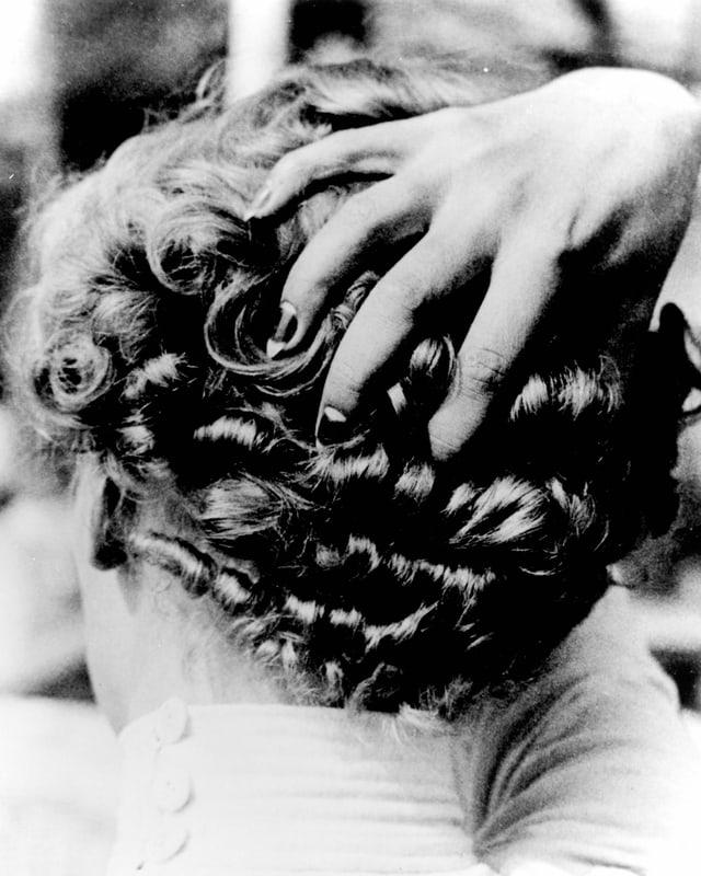 Eine Frau fasst sich mit ihrer Hand an den krausen Hinterkopf.