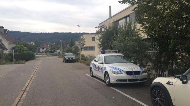 Quartierstrasse mit parkiertem Polizeiauto vor Wohnhäusern.