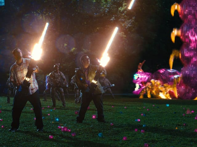 Adam Sandler und Josh Gad schiessen mit einer Lichtkanone in den Himmel.