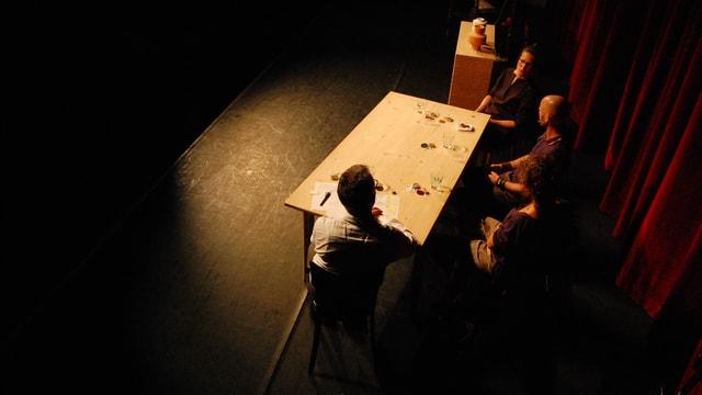 Vier Menschen am Tisch, Scheinwerferkegel.