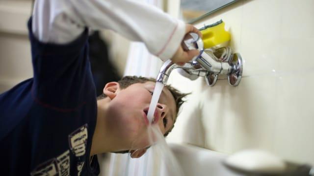 Bub trinkt Wasser aber einem Wasserhahn