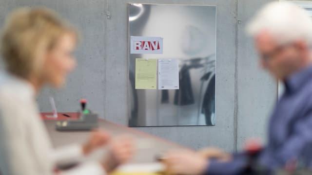 Beratungsgespräch zwischen zwei Personen in einem Arbeitsvermittlungszentrum.