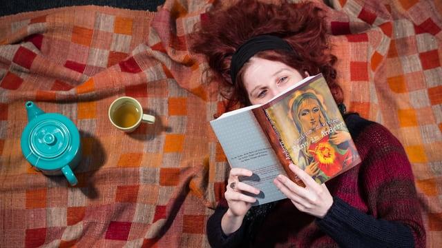 Eine Frau mit rotem Haar liegt auf einer Decke und liest ein Buch.