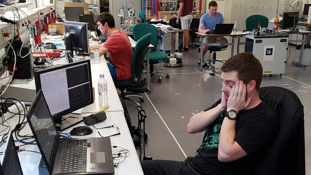 Junge Männer am Computer, einer fasst sich mit beiden Händen an den Kopf.