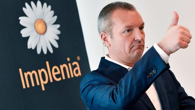 André Wyss vor dem Implenia-Logo, er macht eine Daumen-hoch-Geste.