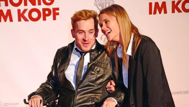 Der querschnittsgelämte Samuel Koch im Rollstuhl, daneben seine Freundin Sarah Elena Timpe. Beide strahlen auf dem roten Teppich.