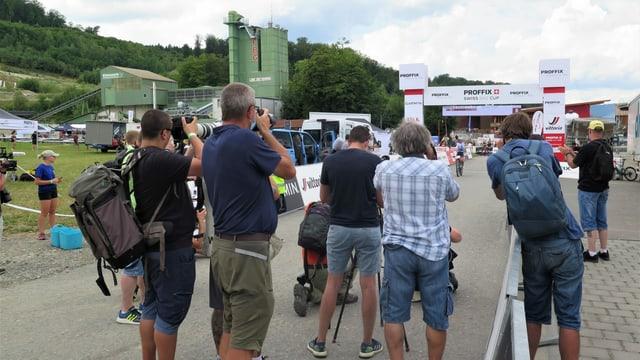 Fotografen stehen hinter dem Ziel, im Hintergrund eine Fahrerin mit erhobenen Händen auf dem Bike