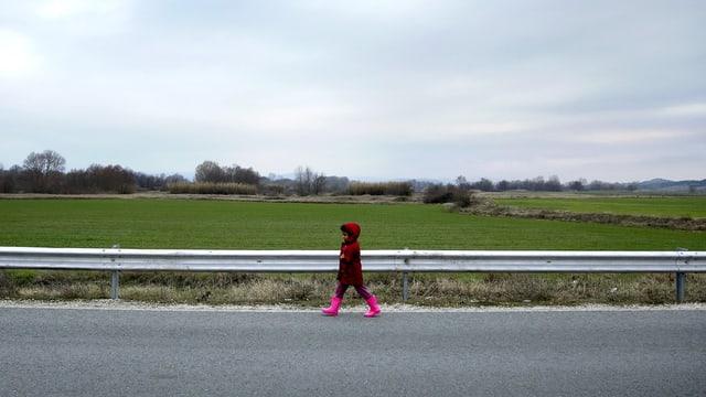Ein Mädchen gehend am Strassenrand, sie trägt eine Kapuze und pinkfarbene Stiefel.