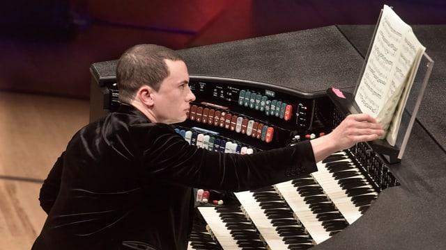 Ein Mann mit kurzgeschnittenen Haaren sitzt an einer Orgel und blättert in der Partitur.