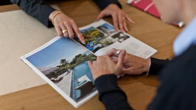 Katalog mit Reisebildern, Hände, die etwas darin zeigen.