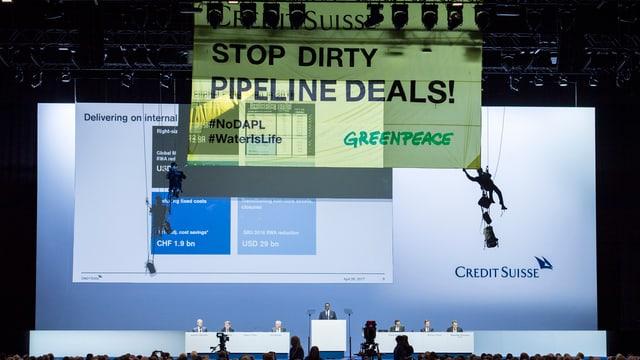 Activists da Greenpeace sa laschan giu vi d'ina suga durant la radunanza generala da la CS.