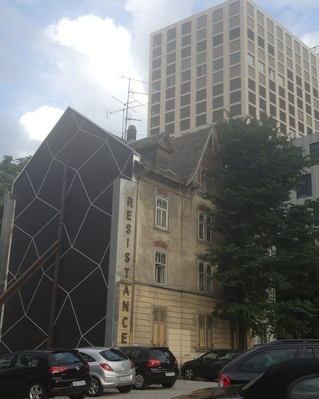 Das Nagelhaus mit Résistance Schriftzug vor dem Hotel Renaissance.