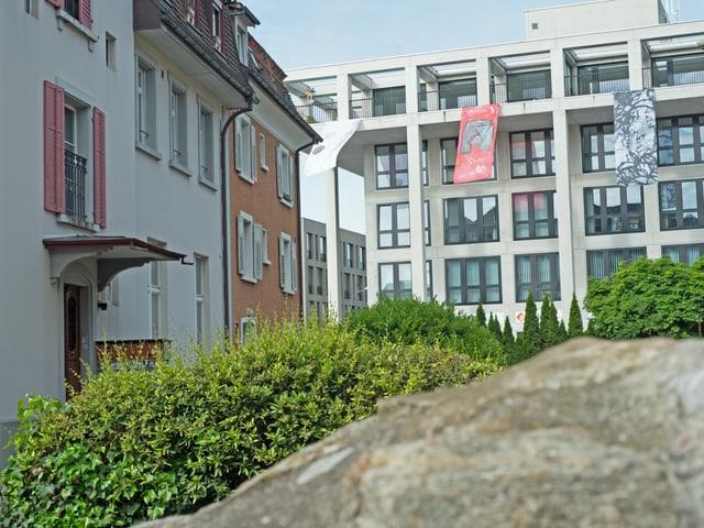 Modernes Mehrfamilienhaus steht neben alten Häusern.