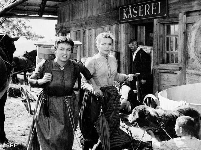 Frauen in Schwarzweiss-Film eilen vor einer Käserei vorbei.