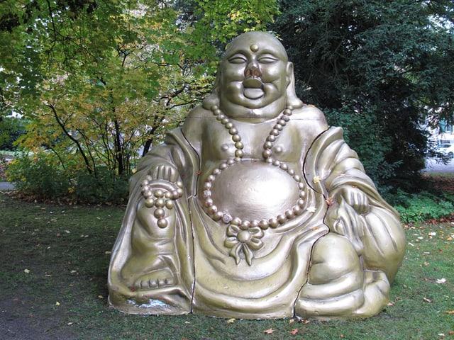 Ein grosser, breiter, goldener Buddha, der lächelt ist auf einer Wiese aufgestellt. Dahinter Bäume und Sträucher.