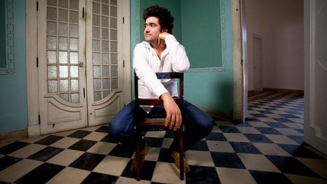 Harold Lopez-Nussa sitzt auf einem Stuhl in einem Raum mit kariertem Boden.