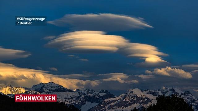 Ufoähnliche weisse Föhnwolken über den Bergen.