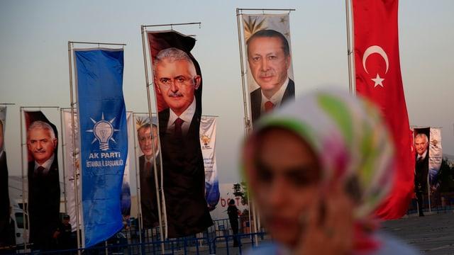 Eine Frau mit Kopftuch am handy, hinter ihr Fahnen mit Erdogan und Yildirim.