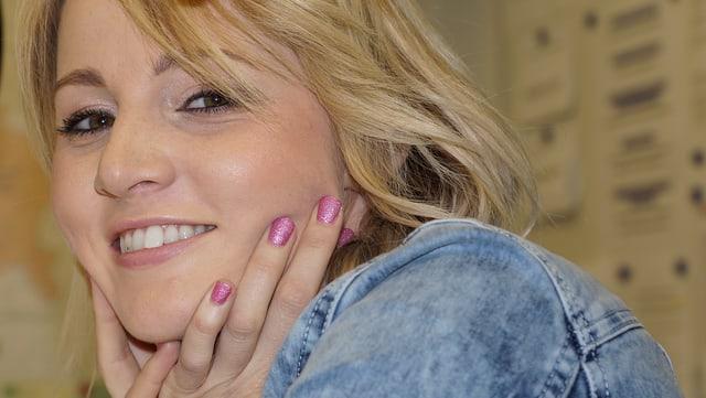 Naschenweng legt ihen Kopf in ihre Hände. Die Fingernägel sin auffällig pinkfarben lackiert.