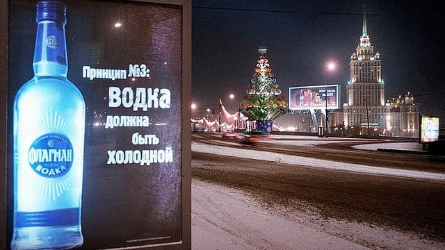 Eine Wodka-Reklametafel an einer Strasse in Moskau, im Hintergrund ein Weihnachtsbaum und ein Gebäude.