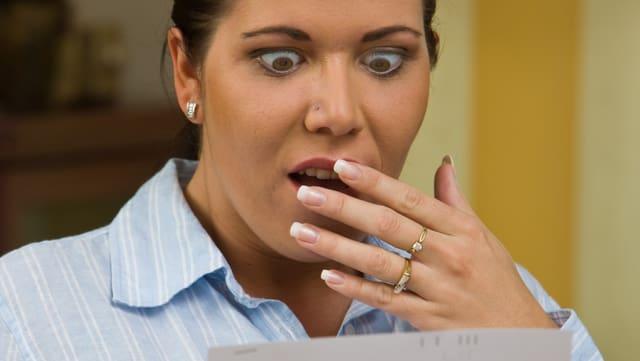 Eine Frau mit Schrecken in den Augen liest eine Rechnung.