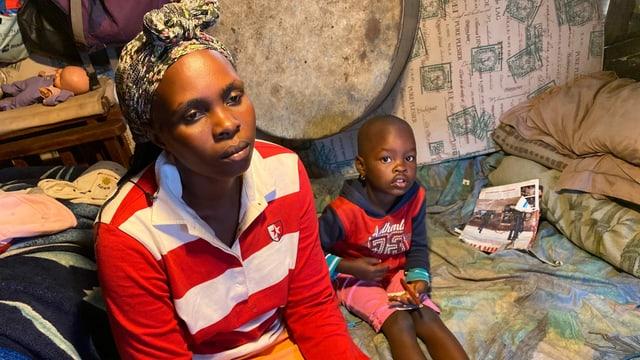 Eine Frau und ein kleines Kind sitzen auf einer Decke.