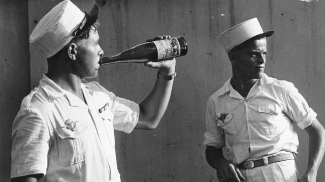 Zwei Soldaten in weisser Ausgangsunifom, einer trinkt Wein aus einer Flasche.