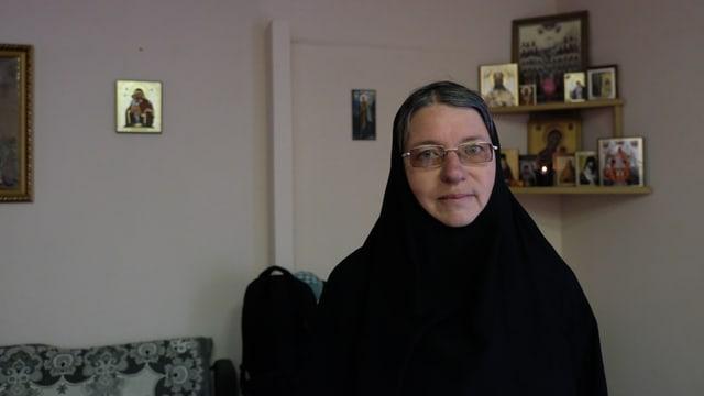 Schwester Nikona in einer schwarzen Robe mit Brille.