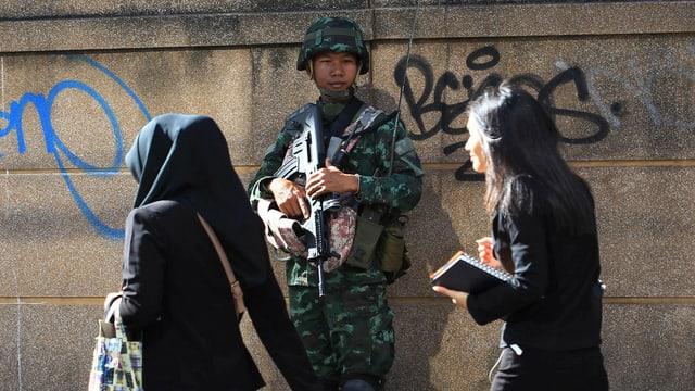 Zwei Frauen gehen die Strasse entlang – im Hintergrund beobachtet von einem Soldaten mit Maschinengewehr.