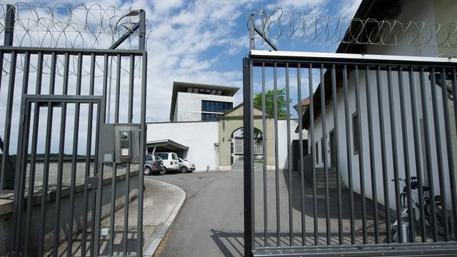 Eingangstor der Strafanstalt mit Stangen und Stacheldraht.