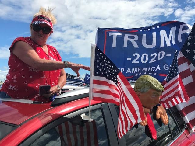 Eine Trump-Anhängerin schaut aus dem mit USA-Flaggen und Trump-Puppe geschmückten Auto.