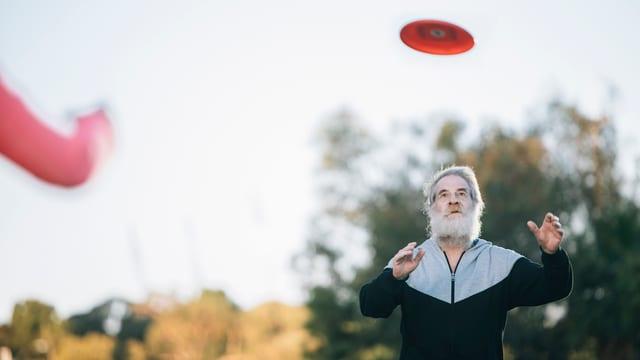 Ein Alter Mann mit graunen Haaren und Bart steht in einem Park und fängt einen Frisbee.