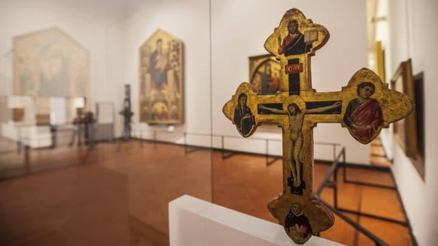 Ausstellungsraum, im Vordergrund ein goldenes Kreuz.