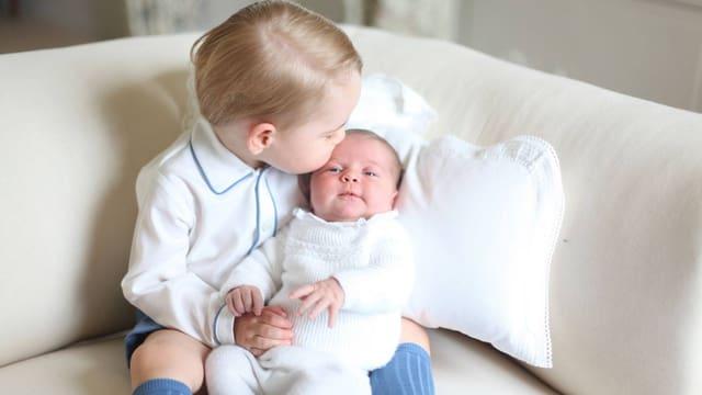 Baby Charlotte sitzt auf Georges Knien. Er küsst Charlotte auf den Kopf.