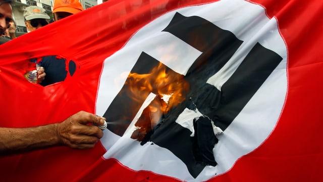 Neonazi-Flagge wird angezündet