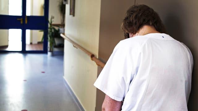 müde, frustrierte Pflegefachfrau lehnt sich in einem Spitalgang an die Wand.
